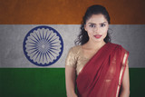 Confident Indian woman with saree posing over Indian flag