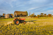 red tractor on the grass of a green field, near an old hut and a grain barn