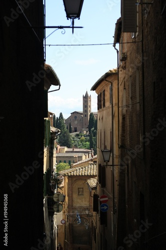 ancient Tuscan walled city houses with towers and stone walls and paved cobbled streets in Italy