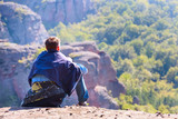 Man looking at mountains panorama view from high rock, travel concept