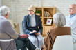 Portrait of blonde female psychiatrist wearing glasses leading group therapy session for senior people in retirement home, copy space