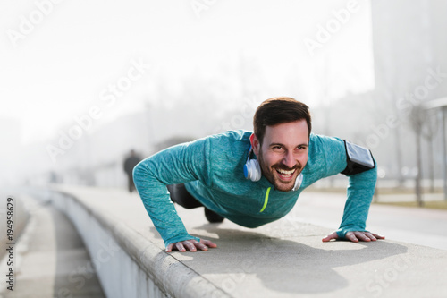 Picture of a young sportsman doing push ups outdoors