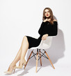 Beautiful young woman in black dress  sitting on chair  against