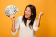 Portrait of a cheerful young woman holding money