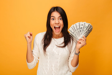 Portrait of an excited young woman holding money banknotes