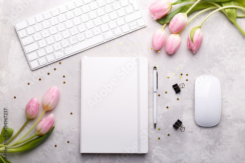 Workspace with keyboard, diary,pen,paper clips and pink tulips on gray stone background, flat lay.
