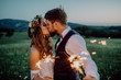 Beautiful bride and groom with sparklers on a meadow.