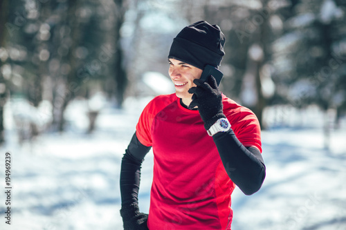 Young Man Taking Break from Jogging in the Forrest using Smart Phone