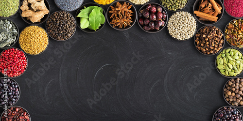 set of spices on  black table with empty space for text. Colorful seasoning against  background of blackboard