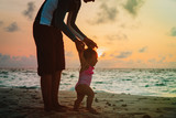 father and little daughter walking on sunset beach - 194970684