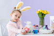 Kid in bunny ears showing colored eggs for Easter
