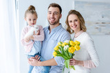 Happy family embracing and holding bunny and tulips - 194973418