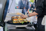 Chef making beef burgers outdoor on open kitchen international food festival event. - 194976807