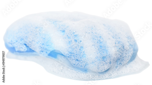 Bar of blue soap in the foam close up isolated