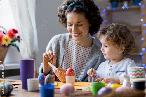 Fototapeta Portrait of happy family painting colorful Easter eggs making decorations sitting at table at home and smiling