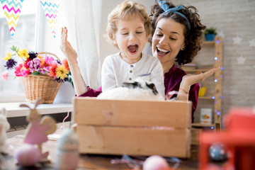 Portrait of excited little boy laughing happily looking at pet bunny  while celebrating Easter with mother