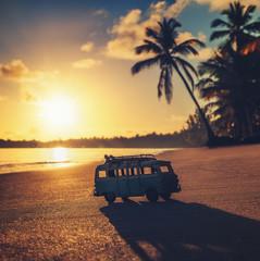 Vintage miniature van on the tropical beach at sunrise