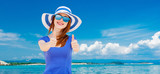 girl in hat and sunglasses on blue sky and sea background