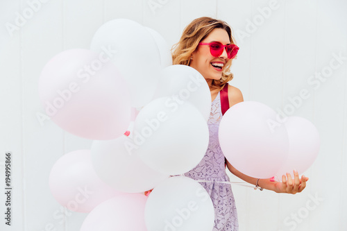 Smiling beautiful girl in pink sunglasses, holds white balloons, enjoying summer. Outdoors.