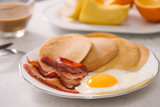 Breakfast plate with pancakes, eggs, bacon and fruit. - 195003099