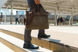 Businessman walking in the city and holding briefcase