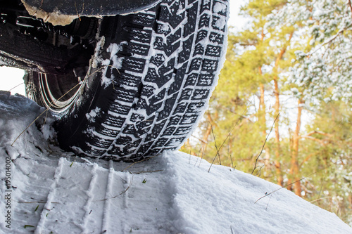Plexiglas Grijze traf. car wheel in the snow, close-up, against the forest