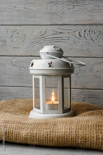 White lantern with a lighted candle inside on a brown tablecloth. Candlestick with decorative stars. Wooden background. Silver gift box next to candles.