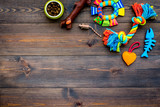 Pet care concept. Toys near bowls with animal feed on dark wooden background top view copy space - 195025045