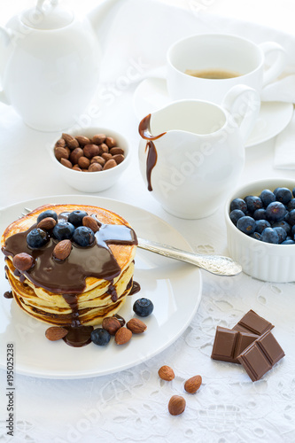 Traditional breakfast concept. Stack of pancakes with chocolate souce, blueberries and nuts on white table cloth. Selective focus