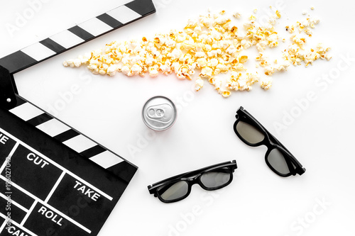 Cinema background. Glasses, popcorn, drink and clapperboard on white background top view