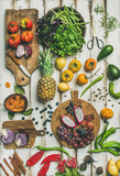 Helathy vegan food cooking background. Flat-lay of Fresh fruit, vegetables, greens and superfoods on boards over white wooden table, top view, vertical composition. Clean eating, alkaline diet concept