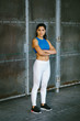 Confident young fit female athlete crossing arms. Sportswoman posing outside. Workout success and healthy lifestyle concept.