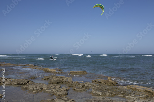 A group of kitesurfers engaged in kiteboarding on sunny day