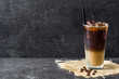 Iced coffee in glass on black stone. Copyspace