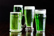 4 beer glasses, stein beer mug, Belgian ale, classic pilsner and English pub with green beer on rustic wood table.
