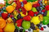 тропические фрукты и ягоды лежат на фоне белых досок