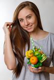 красивая молодая женщина с длинными волосами в серой футболке держит сладкий десерт из цитрусовых фруктов и пироженых макарун