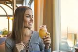 красивая молодая женщина в серой кофте со стаканом напитка в ресторане возле окна и улыбается