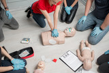 Group of people learning how to make first aid heart compressions with dummies during the training indoors - 195068860
