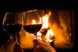 Couple holding pair of glasses with wine at fire pit