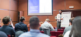 Public Speaker Giving a Talk at Business Meeting. Audience in the conference hall. Skilled coach asks questions to participants of business training. Business and Entrepreneurship concept. - 195087667