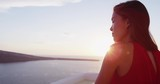 Beautiful woman enjoying the beautiful view of Aegean Sea during sunset. Female tourist is wearing red dress while standing at caldera. She is on her vacation in Santorini. - 195091006