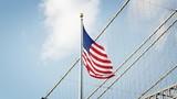American Flag Flying By Brooklyn Bridge In New York - 195099865