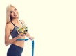 Woman in sportswear with tape measure and salad