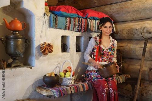 Young woman in a typical Russian wooden log hut