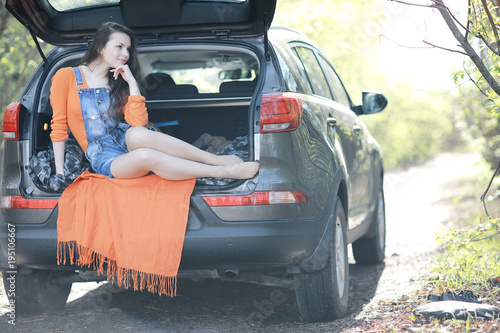 woman sitting in the trunk of the car of a young beautiful spring