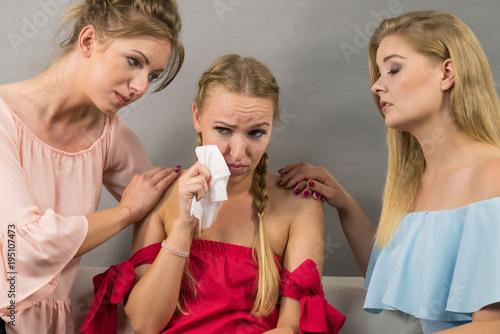 Friends helping sad woman
