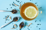 Tea with lemon in a transparent cup. Spoons with different types of teas. Blue background. Pastel colors. Flat lay.  Copy spase