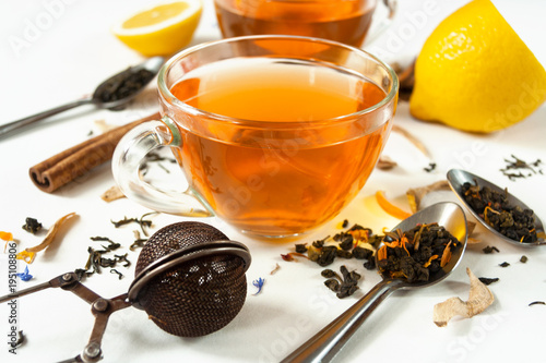 Papiers peints The Two transparent cups of tea with a slice of lemon on a white background. Spoons, a filter for brewing, chopped lemon, cinnamon sticks. Concept. Different types of teas. Close up