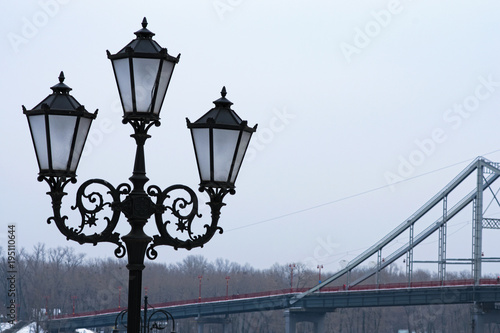 Keuken foto achterwand Kiev Beautiful black street lantern for three lamps, close up photo. Pedestrian bridge in the background. Winter morning view. Kyiv, Ukraine